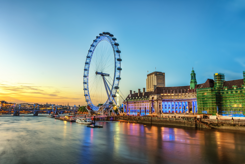 The London Eye on the South Bank of the River Thames at night in London, England